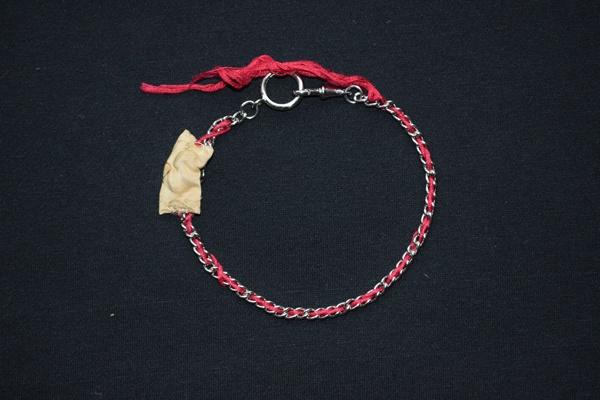 Mongolischer Murmeltierknochen, aufgezogen auf einen roten Seidenfaden und eine Silberkette, als Glücksbringer