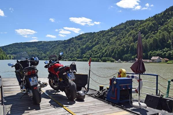 Motorradreisen erleben: Zwei Motorräder auf einer Donaufähre bei einer sommerlichen Überfahrt über den Strom und Blick auf die bewaldeten Donauhänge