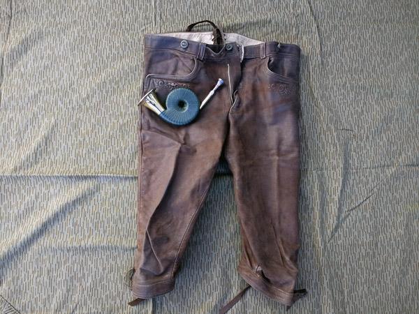 Bild einer lhirschledernen Kniebundhose für die Jagd mit einem Taschenhorn, auf einer Zeltplane liegend