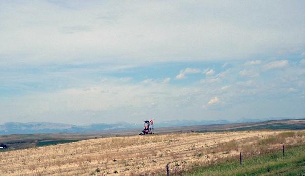 Bild von einer Ölpumpe in Montana an der U.S. Road 89 mit den Rocky Mountains im Hintergrund
