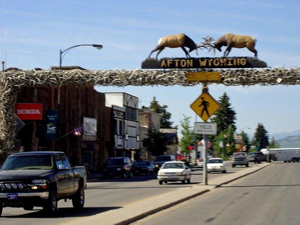 Bild der Hauptstrasse von Afton, WY mit vorbeifahrenden Autos und der Skulptur von zwei verkämpften Hirschen über der Straße