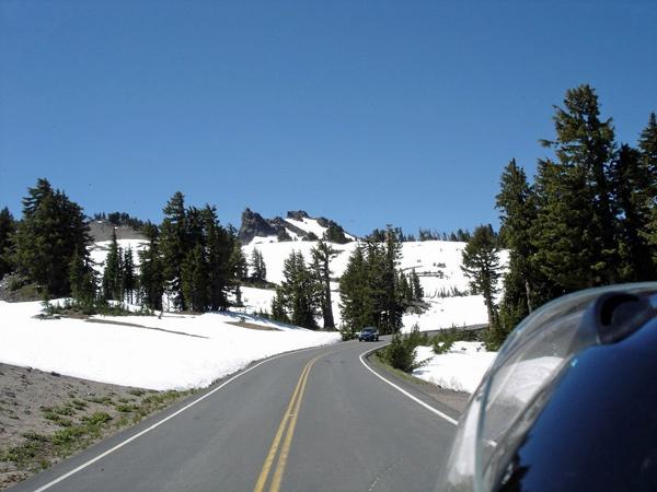 Bild von der Auffahrt zum Crater Lake in Oregon von einem Motorrad aus in schneebedeckter Landschaft mit entgegenkommenden Fahrzeugen