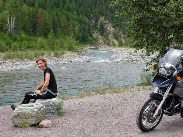 Bild von einer Marschpause am wilden Flathead River in Montana mit einer rothaarigen Motorradfahrerin und einer BMW R 1200 GS