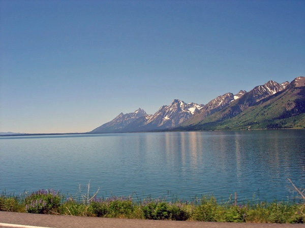 Bild vom Jackson Lake Wyoming mit den Grand Tetons im Hintergrund, vom fahrenden Motorrad aus aufgenommen