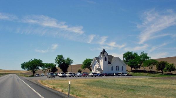 Bild von einer Kirche an der U.S. Route 195 in Washington State mit Autos auf dem Parkplatz davor