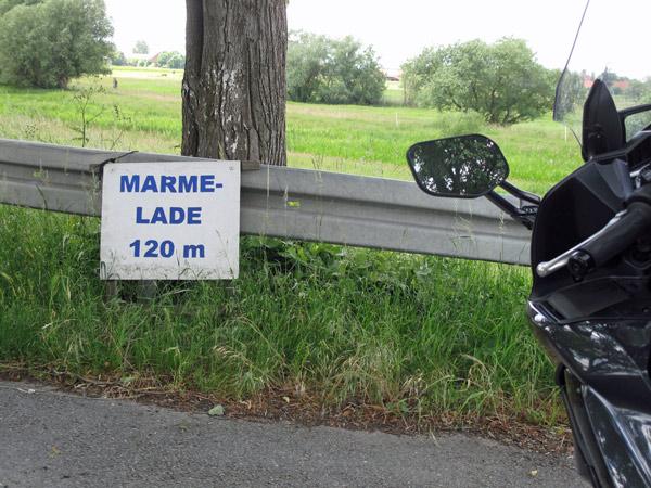 Bild von einem schwarzen Motorrad Yamaha FJR 1300 am Strassenrand vor einem Schild Marmelade 120 m