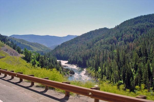 Bild vom Snake River Wyoming mit einer Leitplanke im Vordergrund und einer Bergkette im Hintergrund, vom Motorrad aus aufgenommen