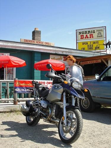Bild von einem Motorrad BMW R 1200 GS mit einer rothaarigen Motorradfahrerin vor der Snorrin' Horse Bar in Norris, MT