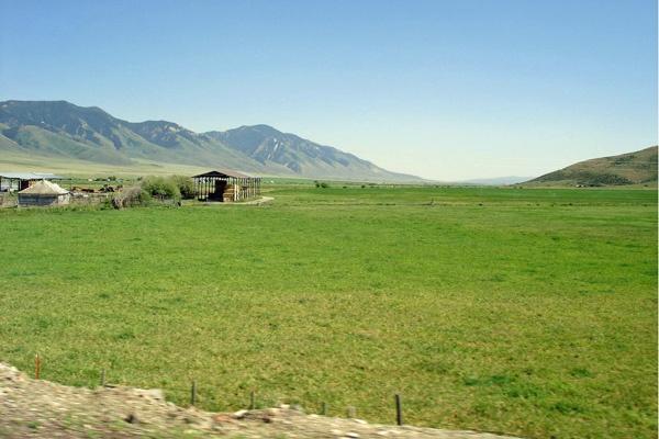 Bild vom Star Ranch Valley Wyoming mit Weide, landwirtschaftlichen Gebäuden und Bergen im Hintergrund