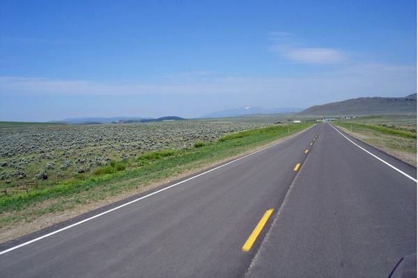 Bild von der U.S. Route 89 Montana in weiter flacher Landschaft mit Bergen am Horizont
