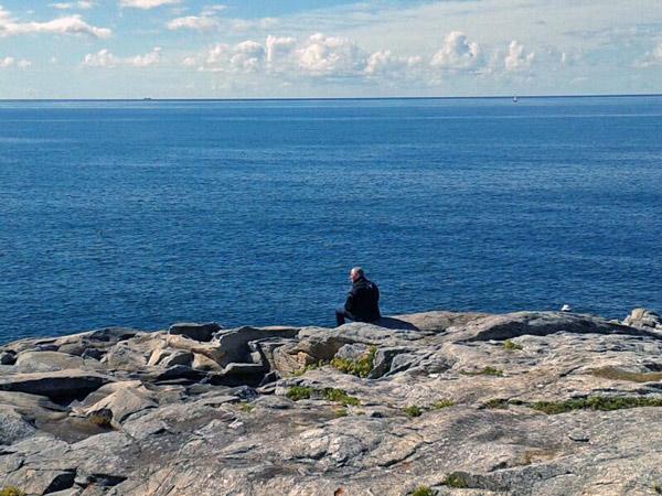 Ensamer Motorradfahrer am Atlantik, auf Felsen sitzend