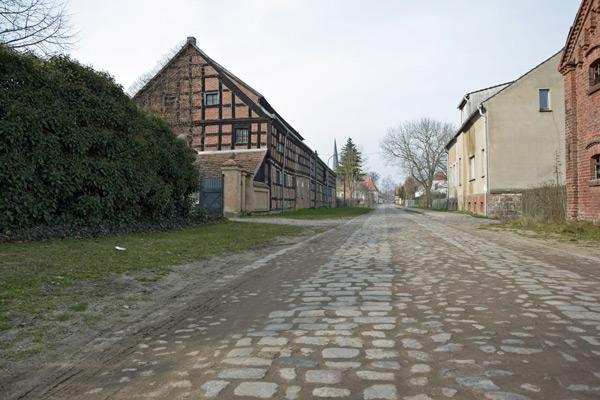 Dorfstraße in Garz (Brandenburg) mit Fachwerkhaus und Pflasterung