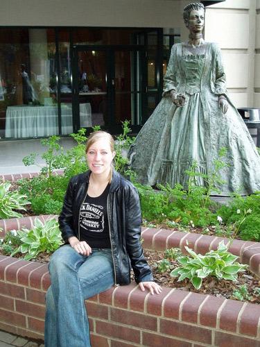 Blonde junge Frau vor der Statue der Herzogin Charlotte in Charlotte, NC