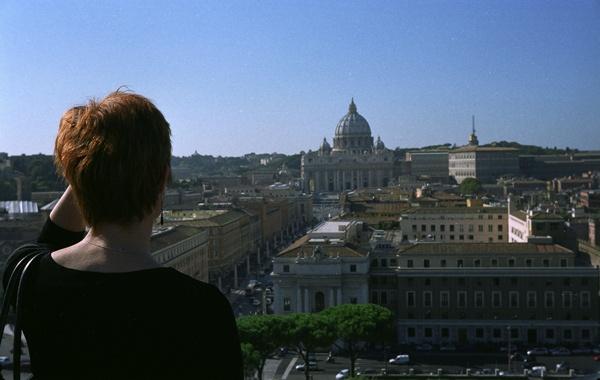Rothaarige Motorradfahrerin beim Blick auf den Petersdom