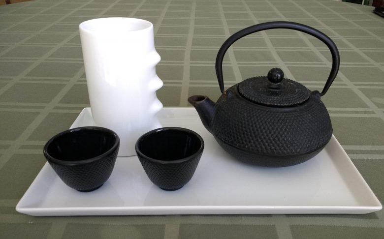 Eiserne japanischen Teekanne mit zwei eisernen Teeschalen auf einem weißen Porzellantablett