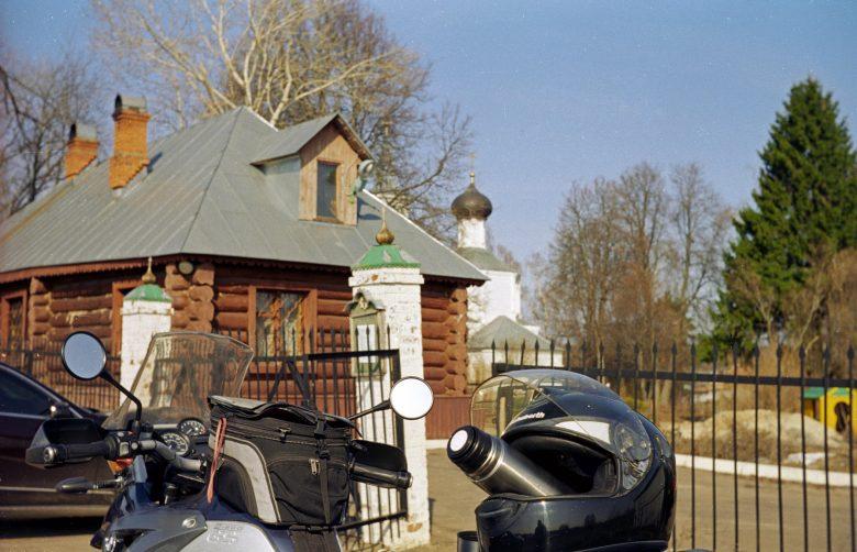 Russische Dorfkirche mit einem Motorrad BMW R 1200 GS im Vordergrund und einer orthodoxen Kirche im Hintergrund