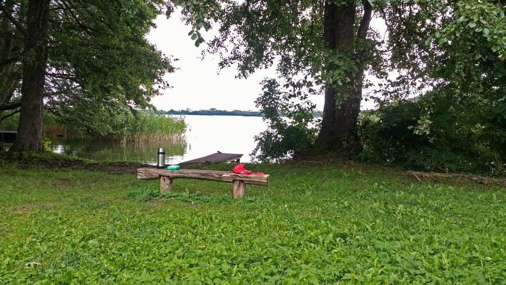 Holzbank mit Thermosflasche am Seeufer unter Bäumen bei einem Picknicks
