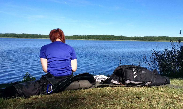 Einer der erholsamen Picknickplätze für den Sommer: Rothaarige Motorradfahrerin mit blauem Hemd bei einem Picknick am Mellensee, Lkr. Teltow-Fläming in Brandenburg