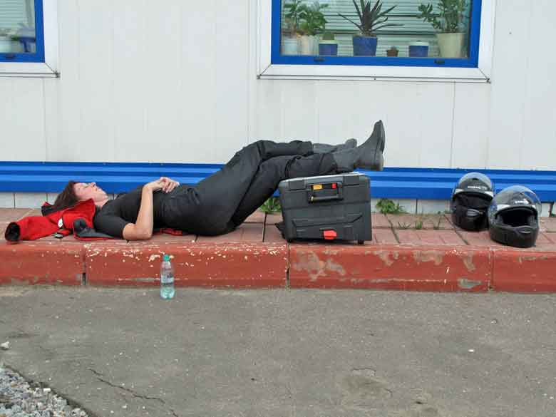 Rothaarige Motorradfahrerin an einer Tankstelle Russland bei einer Ruhepause auf dem Boden liegend als Erinnerung daran, eine Motorradtour umsichtig zu planen