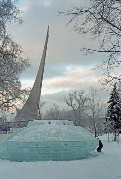 Raketendenkmal am Kosmonautenmuseum in Moskau im Winter mit einer aus Eis gebauten Raumkapsel im Vordergrund