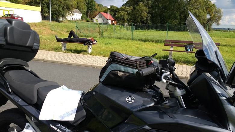Rothaarige Motorradfahrerin auf einer Bank liegend mit einem Motorrad im Vordergrund bei einer Ruhepause an der Fähre Gozdowice an der Oder bei einer Motorradtour in die Neumark