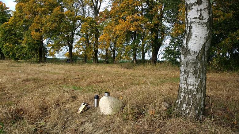 Thermosflasche mit Picknick und einem Feldstein auf dem Schlachtfeld von Zorndorf (Sarbinowo) aus dem Siebenjährigen Krieg bei einer Motorradtour in die Neumark