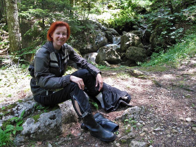 Rothaarige Motorradfahrerin auf einem Stein sitzend bei der Rast an einer Bergquelle bei einer Motorradtour in die Chartreuse