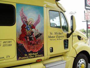 Gelber Truck mit dem Schutzengel St. Michael auf der Beifahrerseite