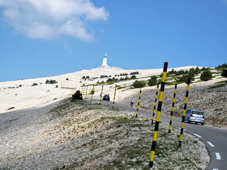 Auffahrt zum Gipfel des Mont Ventoux mit schwarz-gelben Begrenzungsstangen am Strassenrand, Autos, Radfahrern und Bergstation im Hintergrund