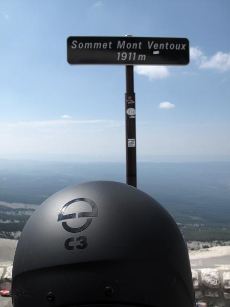 Gipfelschild am Mont Ventoux mit der Anzeige 1911 m und Fernsicht über das Land mit einem schwarzen Motorradhelm Schuberth C3 im Vordergrund