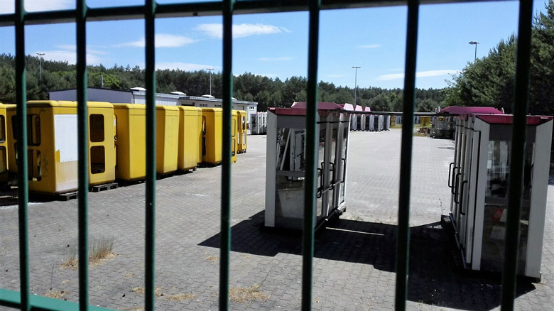 Bild vom Telekom-Telefonzellenlager in Michendorf, Landkreis Potsdam-Mittelmark (Brandenburg) mit den alten gelben und den neueren magentafarbenen Telefonzellen hinter einem Gitterzaun