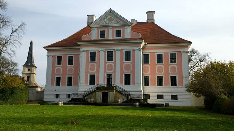 Schloss Gross Rietz, Parkansicht, mit renovierter rosa Fassade und dem Turm der Dorfkirche im Hintergrund