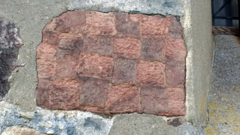 Roter Schachbrettstein an der Kirche von Herzberg in der Niederlausitz
