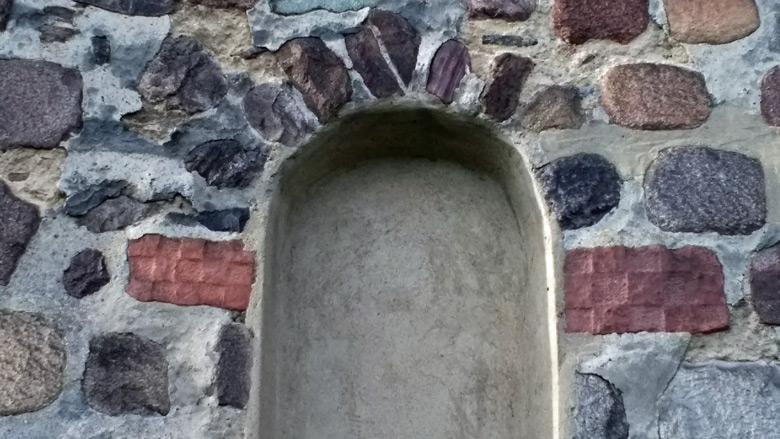 Rote Schachbrettsteine an der Kirche von Herzberg neben einem Fensterbogen an der Suedostwand des Gebäudes, entdeckt auf einer Lausitztour mit dem Motorrad