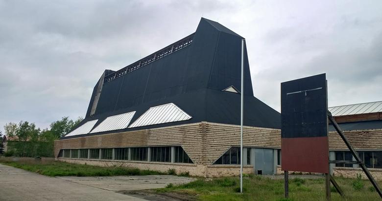Ehemalige Hutfabrik Luckenwalde Seitenansicht mit einem lang gestreckten Gebäude mit hohem schwarzen Aufbau uns einem mit Büschen bewachsenen Vorplatz im Vordergrund