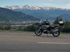 Bild von der Auffahrt zum winterlichen Vercors mit einer BMW R 1200 GS im Vordergrund und der Schneebedeckten Alpenkette im Hintergrund, dazwischen der Talkessel mit der Stadt Grenoble in Frankreich