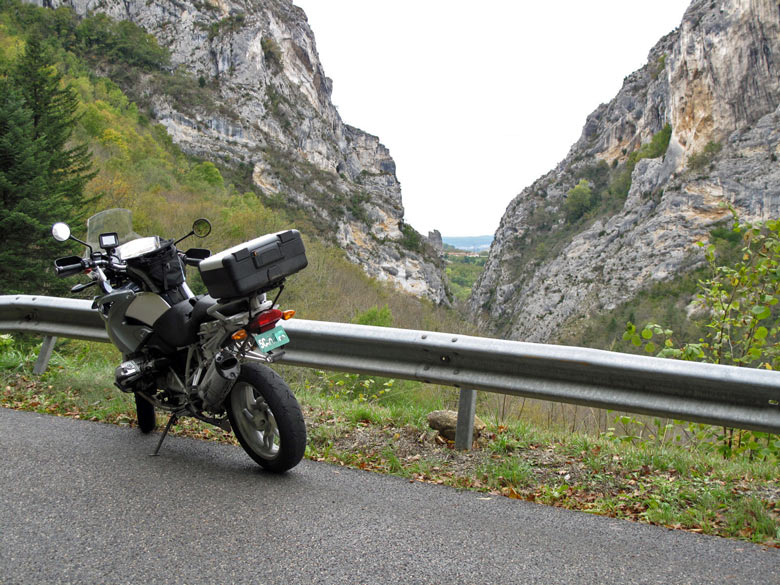 Ausblick durch Felsen auf das Tal der Isère mit einer BMW R 1200 GS im Vordergrund und dem Tal der Saône in der Ferne bei einer Motorradtour durch den winterlichen Vercors