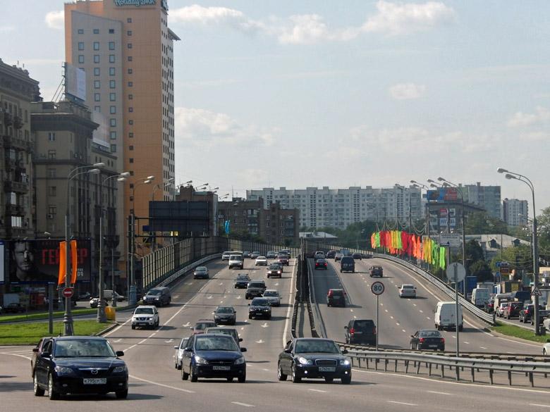 Dritter Verkehrsring in Moskau mit zwei Richtungsfahrbahnen und schwachem Autoverkehr, Plattenbauten und festlichem Fahnenschmuck , gesehen beim Motorradfahren in Moskau und der Provinz