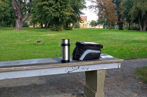 Bild von einem Tankrucksack auf Parkbank mit einer Thermosflasche und einem Blick auf ein Schloss im Hintergrund