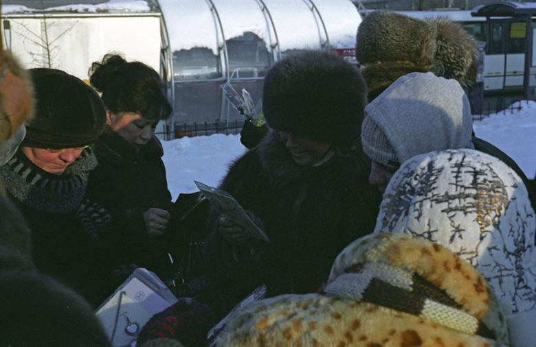 Einkäuferinnen im Pelzmantel auf einem Moskauer Markt im Winter, das Angebot an Modeschmuck und Strümpfen studierend