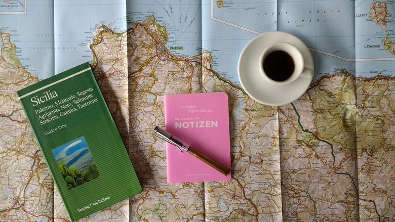 Vor der Solo-Motorradtour: Kartenstudium Sizilien mit einer Landkarte der Provinz Palermo, einem Teiseführer, einem Notizbuch mit Füller und einer Tasse Espresso