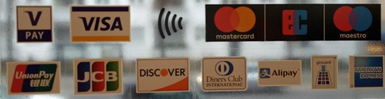 Motorradtour planen: Logos von Kreditkarten an der Glastür eines Geschäfts