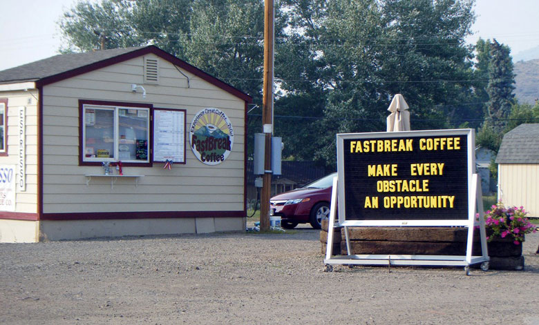 """Motorradreisen erleben, auch wenn sich die Pläne ändern: Schild neben einem ländlichen Café mit der Aufschrift """"Make Every Obstacle An Opportunity"""", gesehen in Lakeview, OR (USA)"""