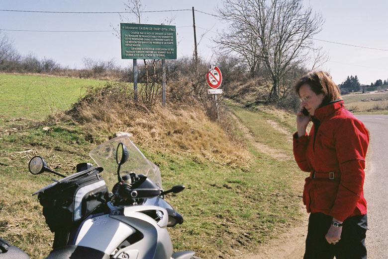 Rothaarige Motorradfahrerin in einer roten Jacke und schwarzer Hose mit einer BMW R 1200 GS bei einer Marschpause auf der Motorradtour zum Hutmuseum in Chazelles-s.-L.