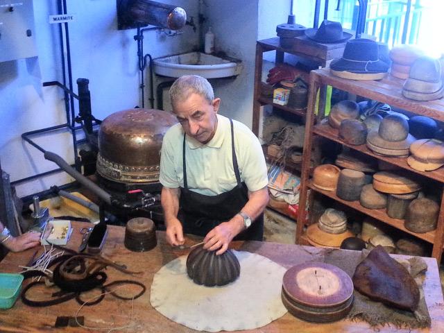 Hutmacher bei der Arbeit mit verschiedenen Formen und einem Dämpftopf im Hintergrund