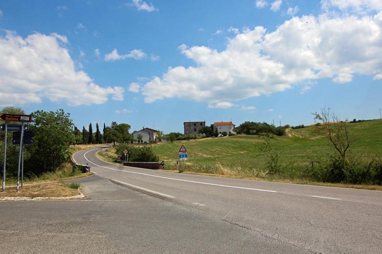 Motorradtour Toskana - Rom Via Cassia zwischen Viterbo und Orvieto mit Strassenschildern und Häusern im Hintergrund