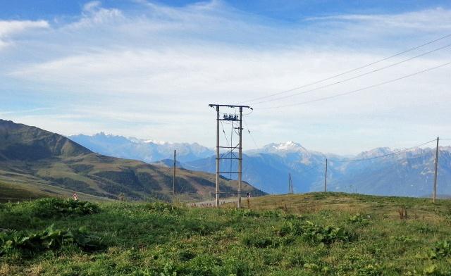 Bergblick vom Col de la Madeleine mit Strommasten im Vordergrund und der teilweise schneebedeckten Lauzière-Kette im Hintergrund