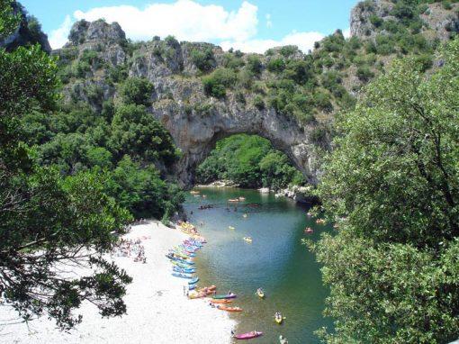 Bild vom Pont-de-Vallon, besucht bei einer Motorradtour durch die Ardèche, mit bunten Kanus auf dem Wasser im Vordergrund