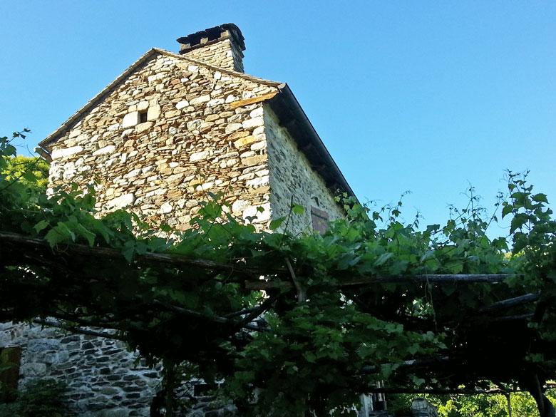 Steinernes Bauernhaus mit Weinranken bei einer Motorradtour durch die Ardèche