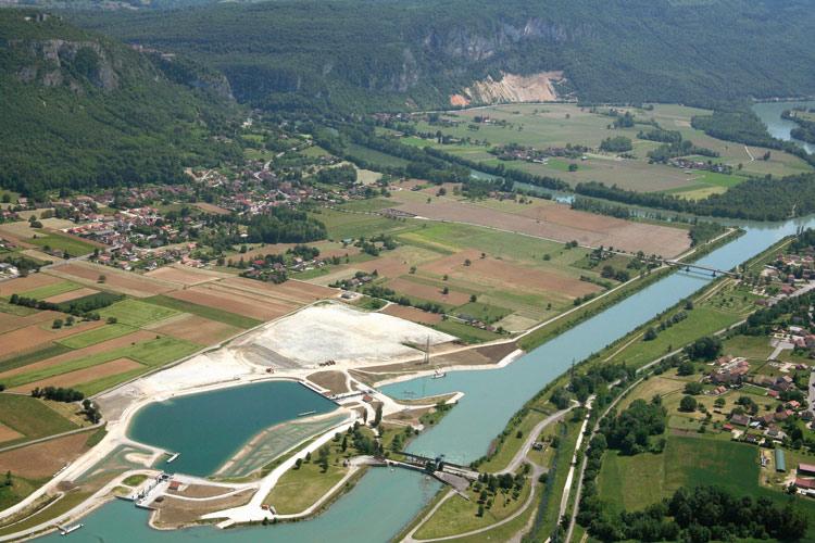 Luftaufnahme vom Wasserkraftwerk Brens-Virginin im französischen Département Ain mit dem Vorgebirge Bugey im Hintergrund